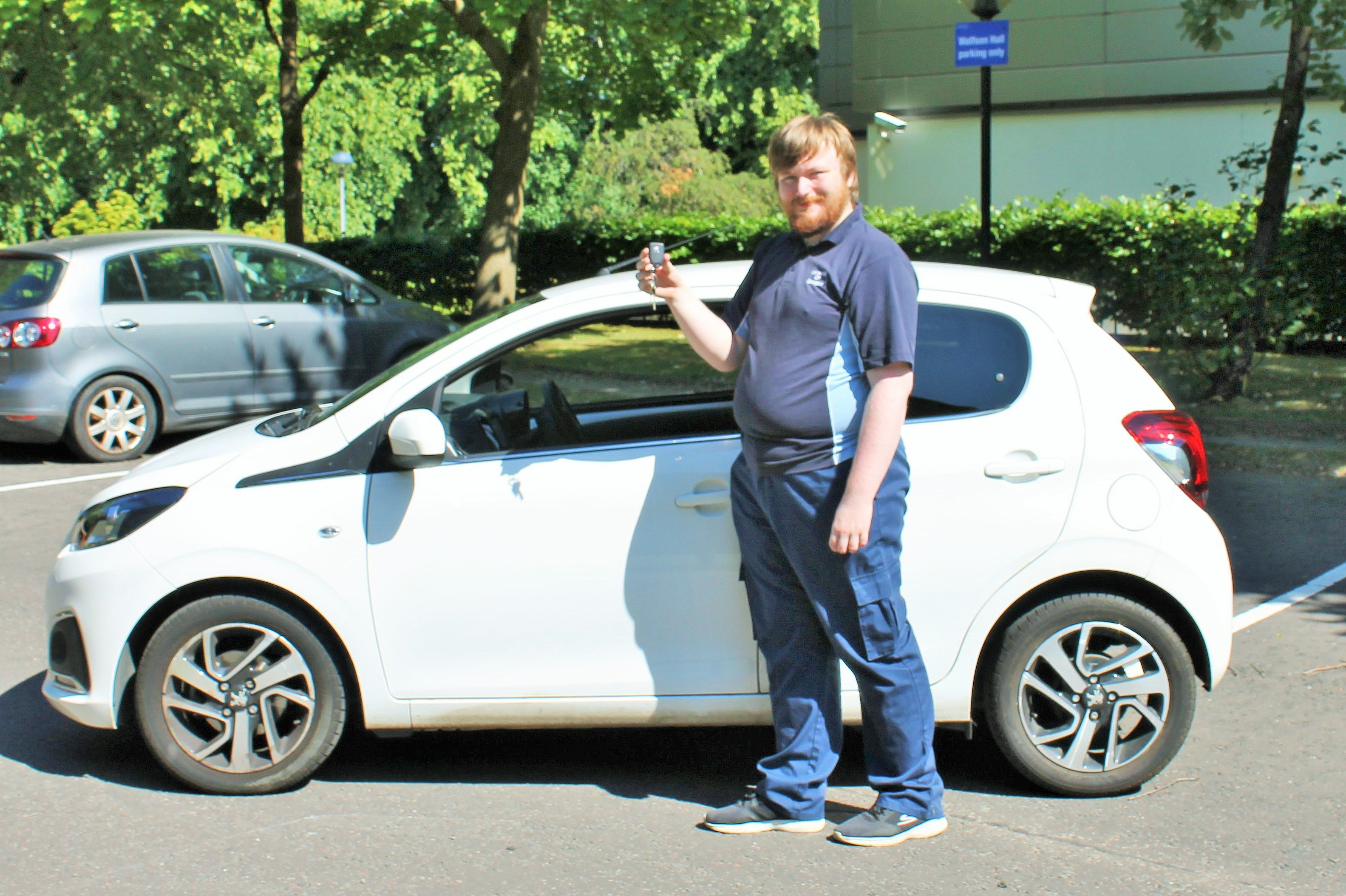 Darren McCluskey with the new car his job has helped him buy.