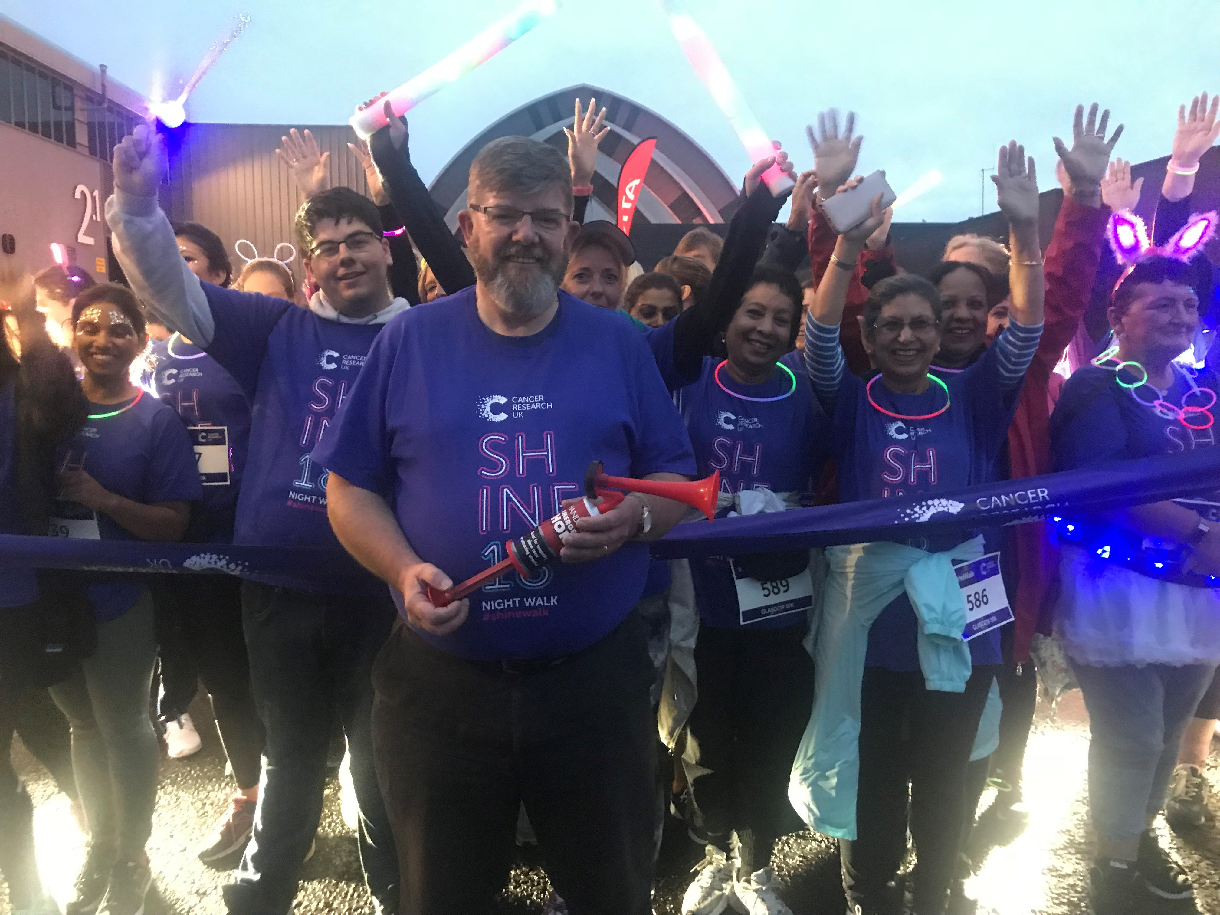 Cancer survivor Ian Anderson sounds the horn at the start of Shine Glasgow, a 10K night-time walk through Glasgow